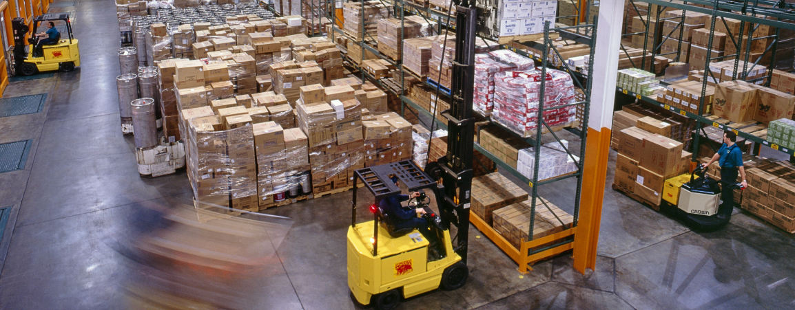 Motion blur of forklifts working in a restaurant distribution warehouse